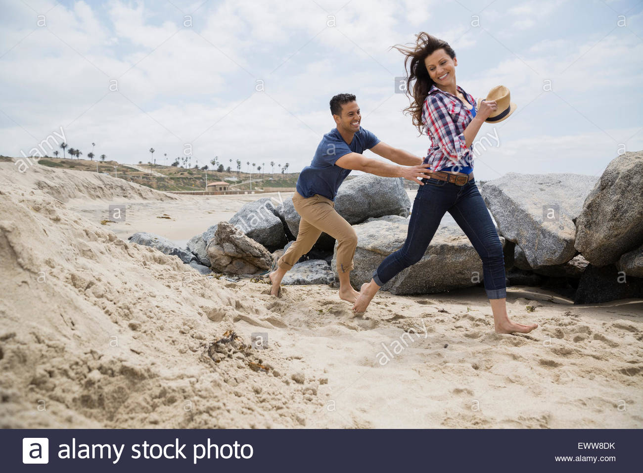 Playful couple running on beach - Stock Image