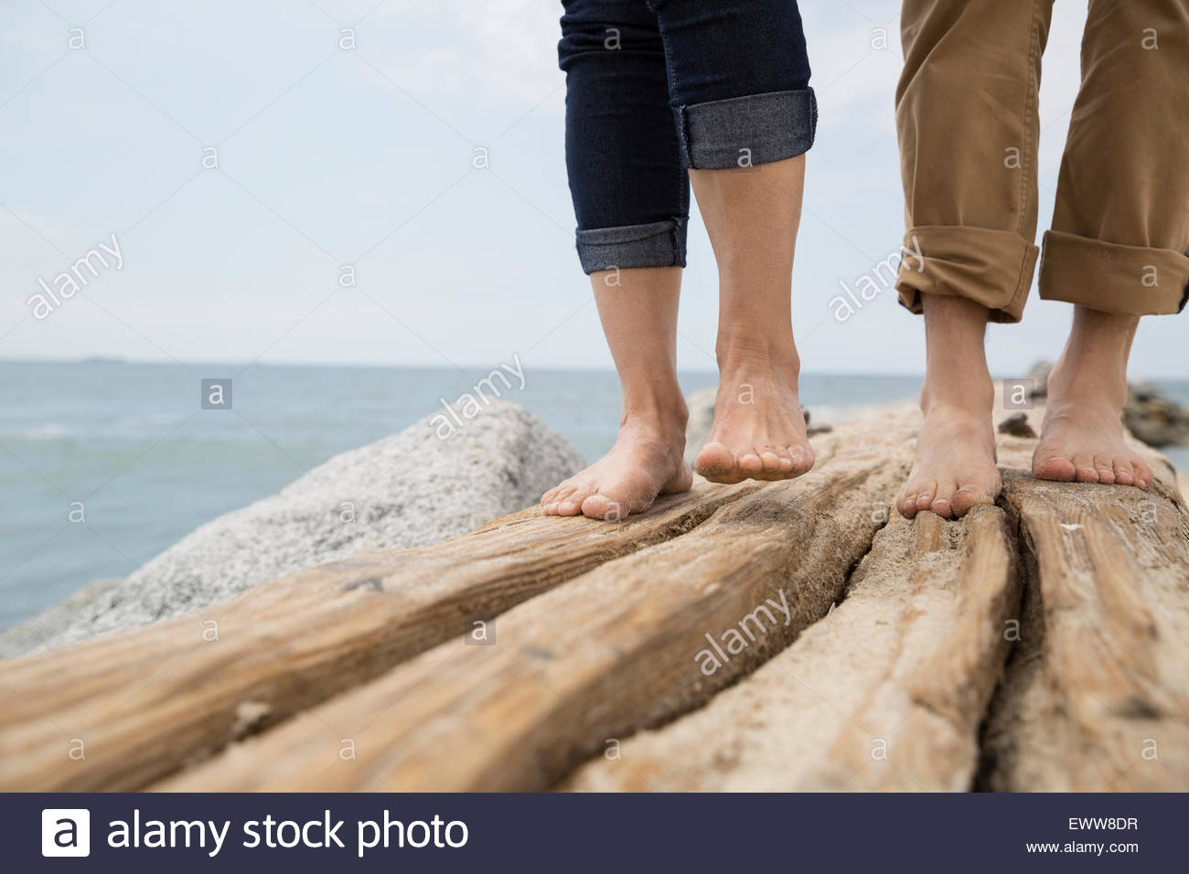 Close up bare feet of couple on ocean jetty - Stock Image