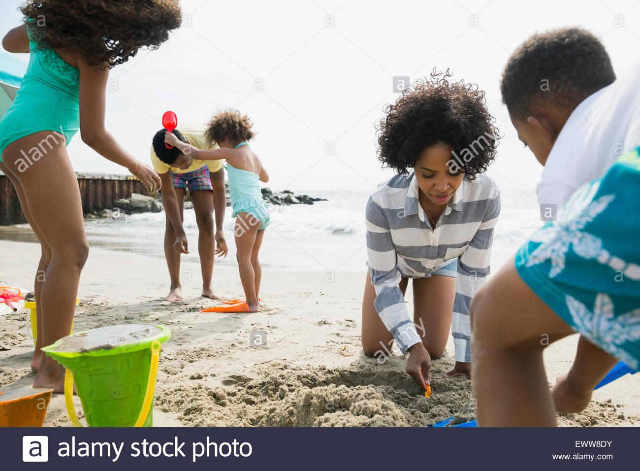 Family making sandcastle on beach - Stock Image