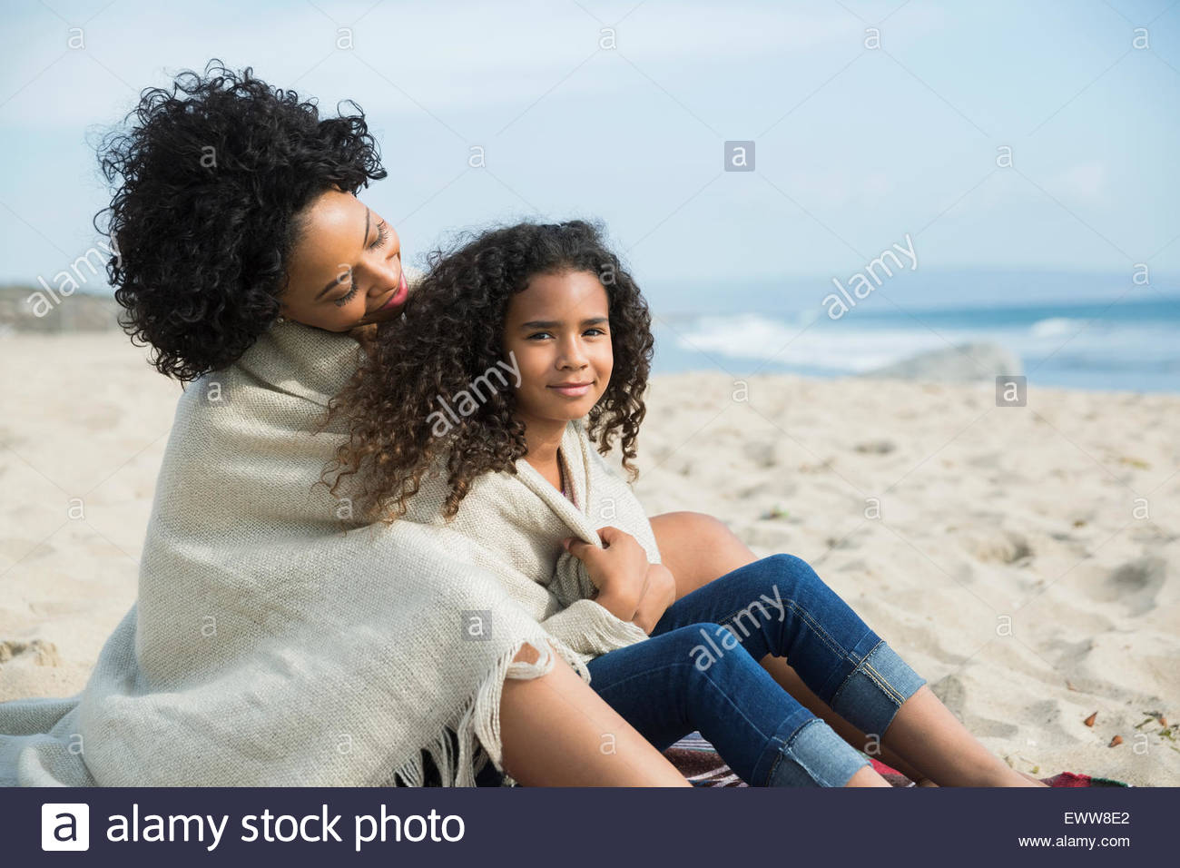 Mother and daughter wrapped in blanket on beach - Stock Image