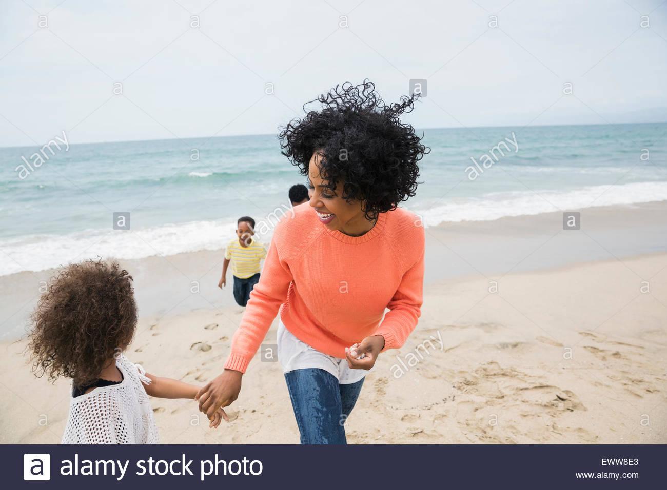 Family walking on beach - Stock Image