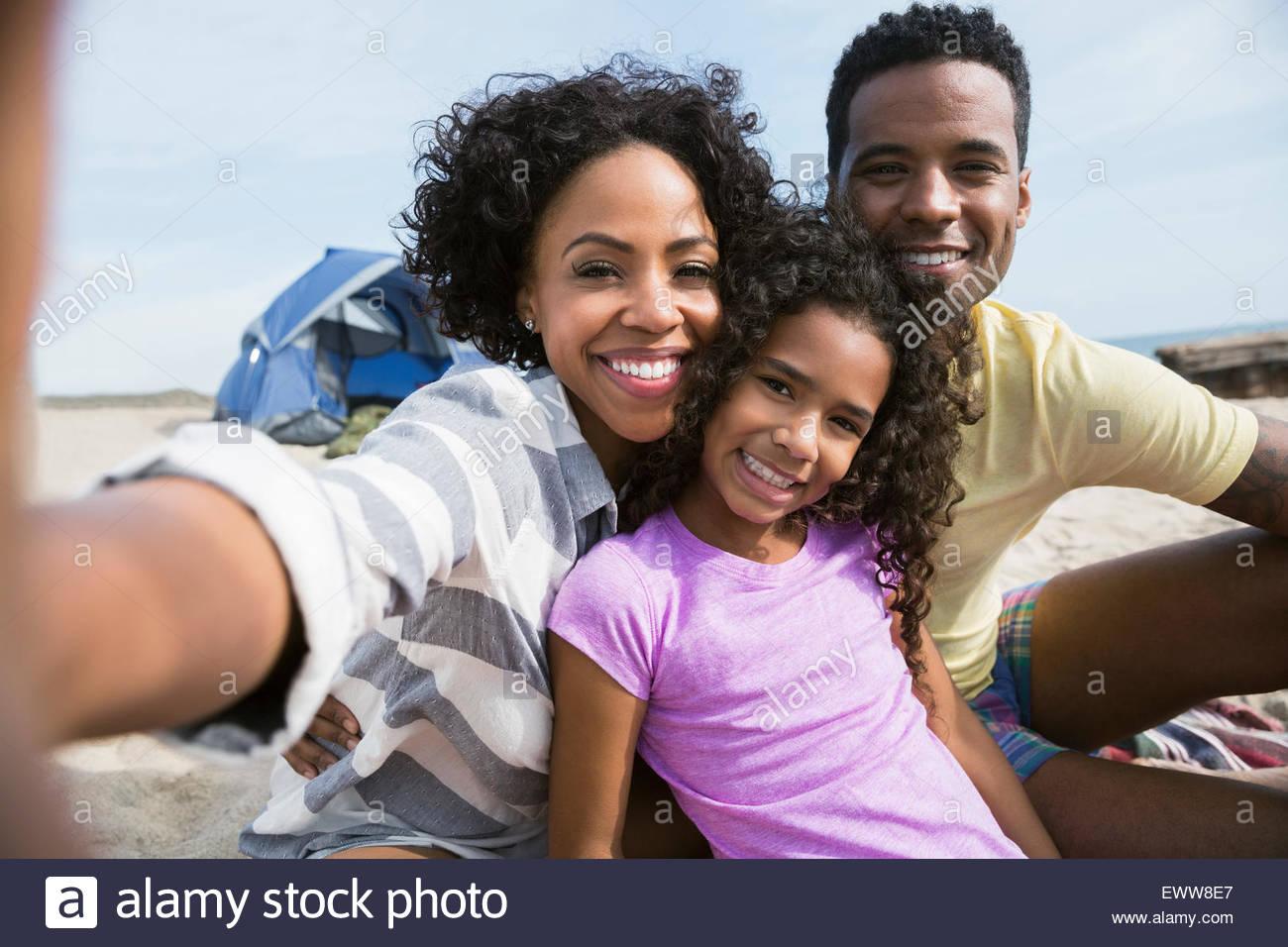 Portrait smiling family on beach - Stock Image