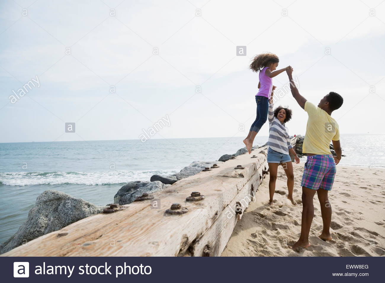 Father and mother helping daughter jump beach wall - Stock Image