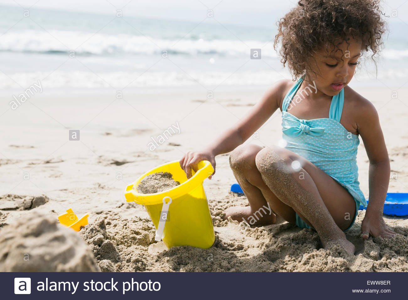 6f615b88430 Girl in bathing suit making sandcastle on beach - Stock Image