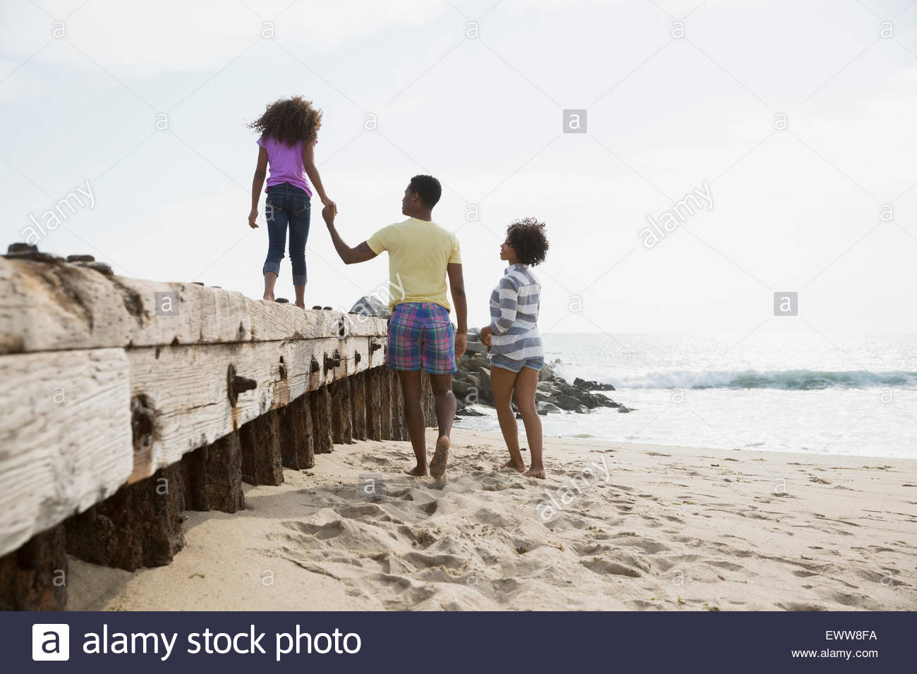 Family walking along beach wall - Stock Image
