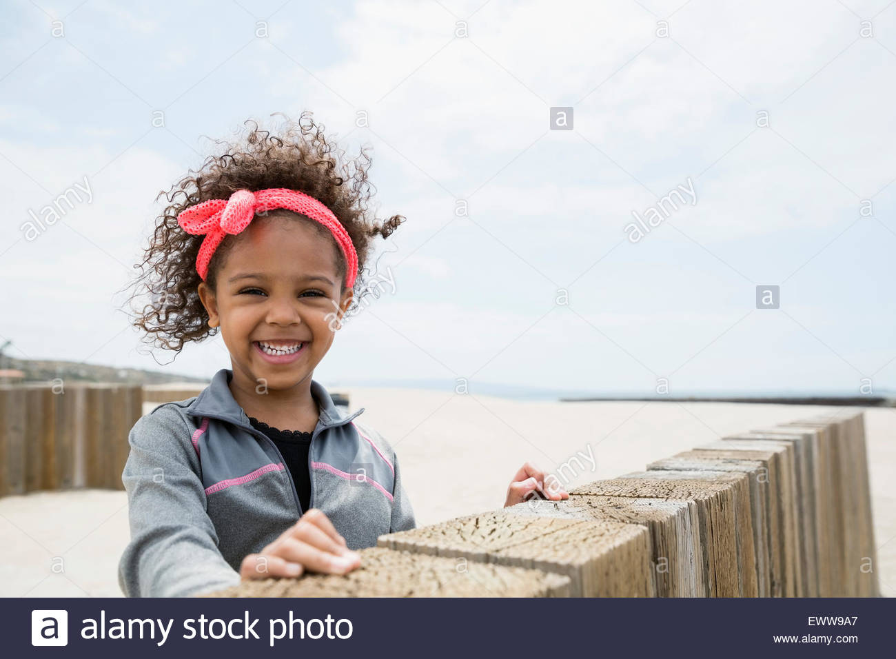 Portrait smiling girl curly hair at beach wall - Stock Image