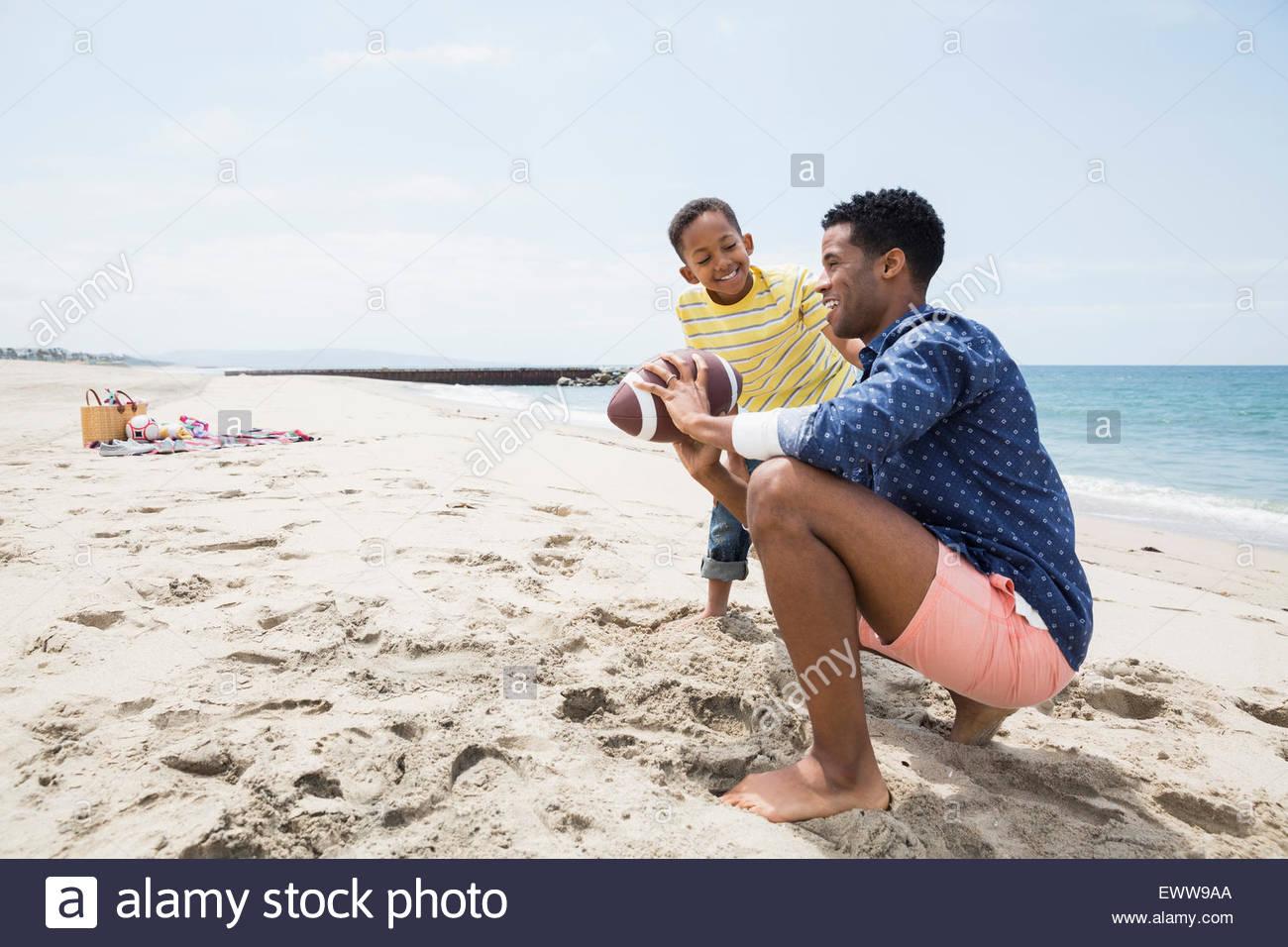 Father teaching son football grip on beach - Stock Image