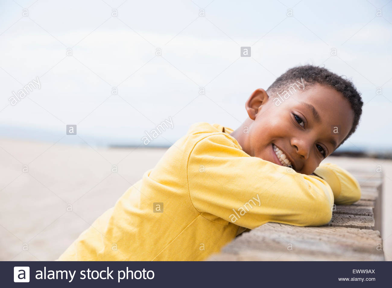 Portrait smiling boy leaning on beach wall - Stock Image