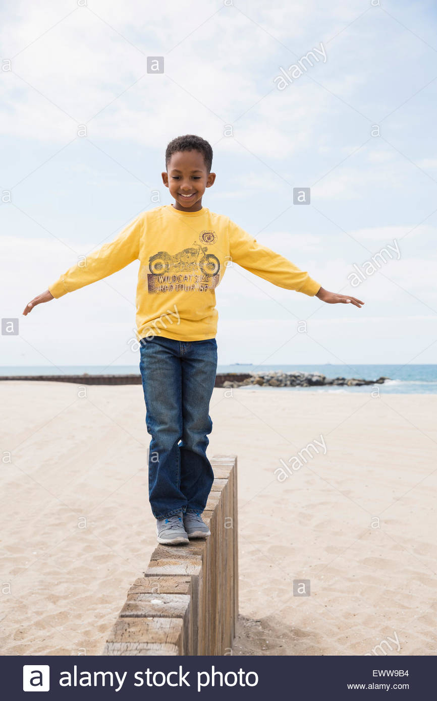 Smiling boy balancing on beach wall - Stock Image