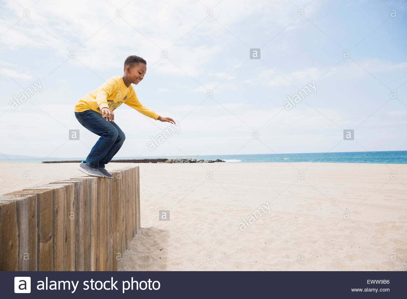 Boy jumping from beach wall - Stock Image