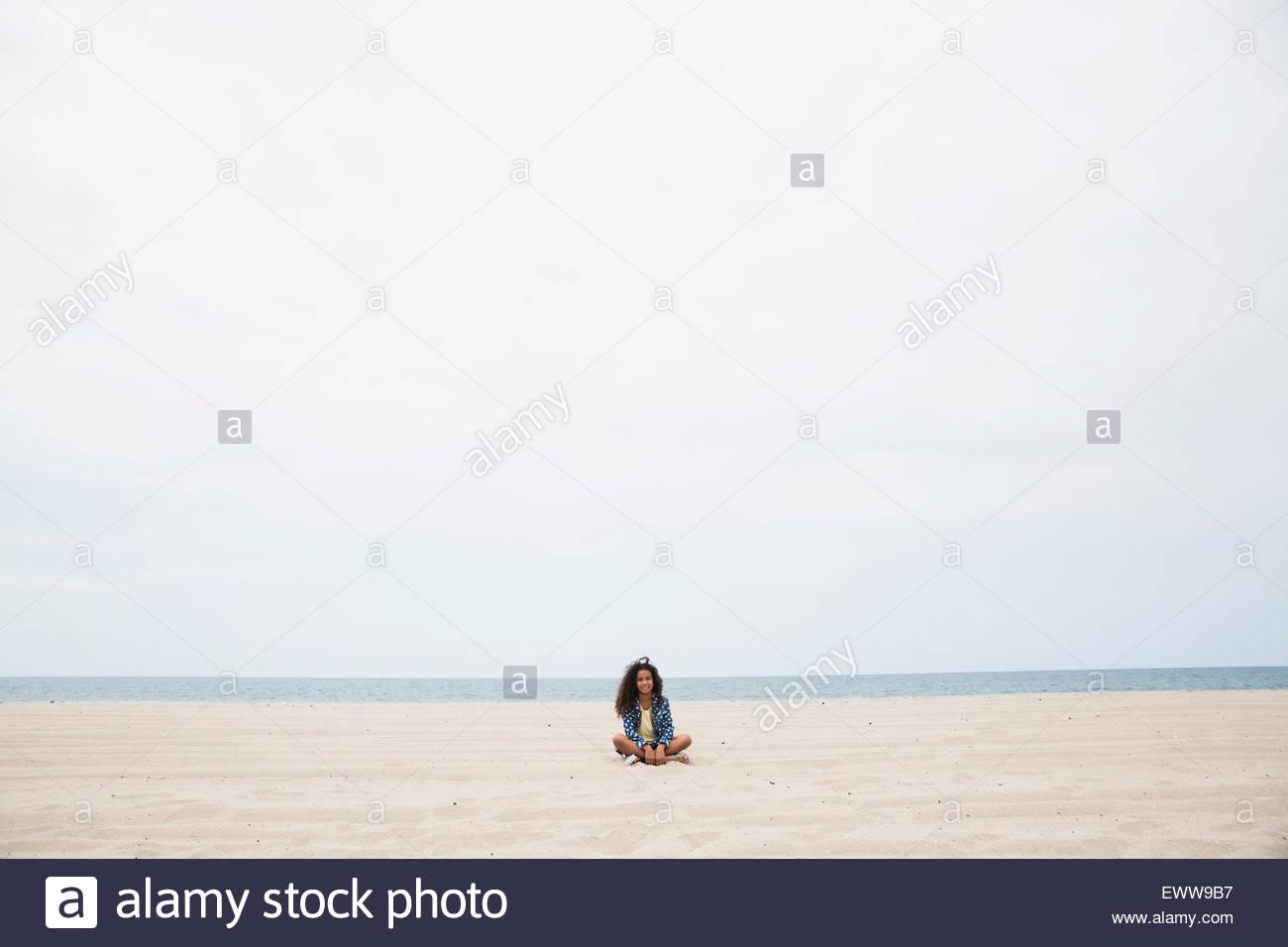 Portrait girl sitting cross-legged on beach - Stock Image