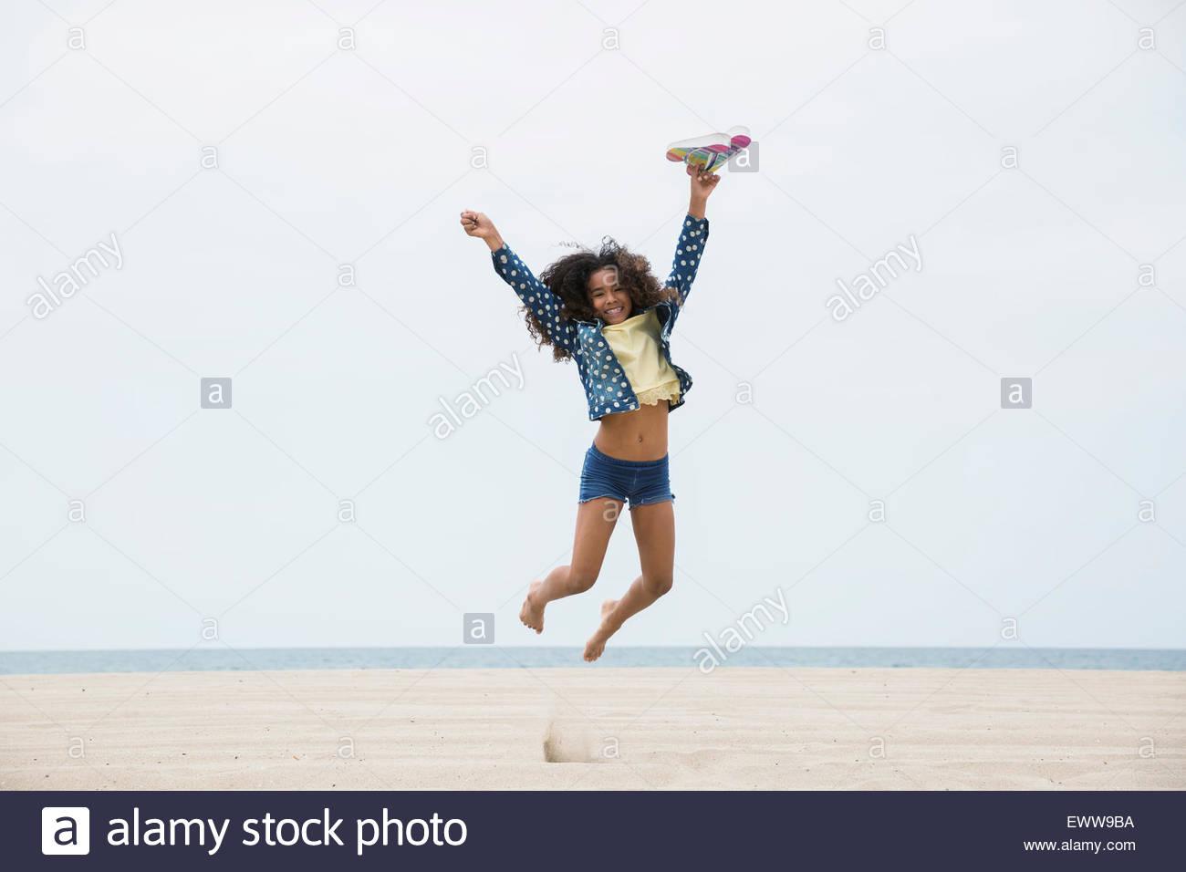 Portrait exuberant girl jumping on beach - Stock Image