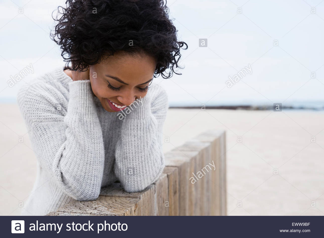 Smiling woman curly black hair leaning beach wall - Stock Image