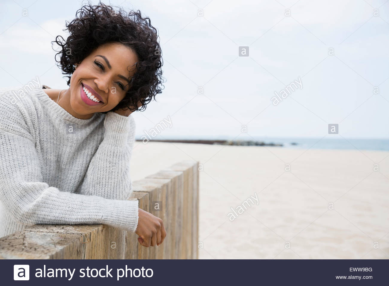 Portrait smiling woman curly black hair beach wall - Stock Image