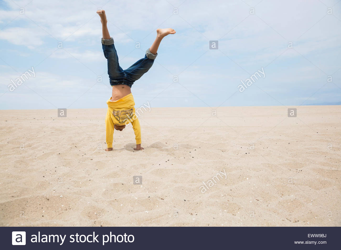 Boy doing handstand on beach - Stock Image