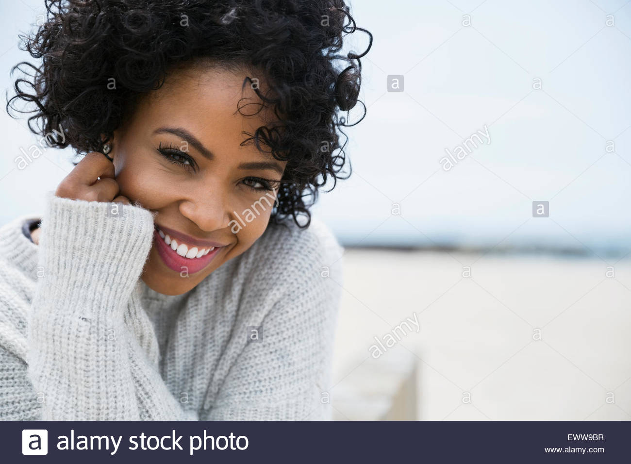 Portrait smiling woman curly black hair at beach - Stock Image