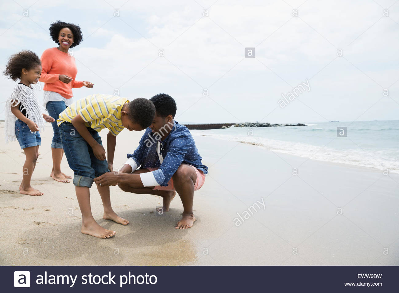 Father helping son roll up jeans at beach - Stock Image