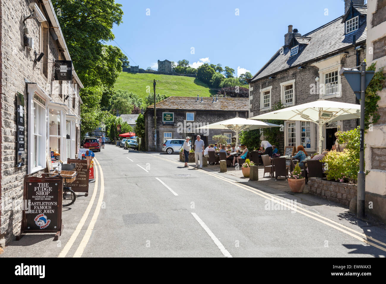 Shops and a pub in Castleton with Peveril Castle overlooking the village in Summer, Derbyshire, Peak District National - Stock Image