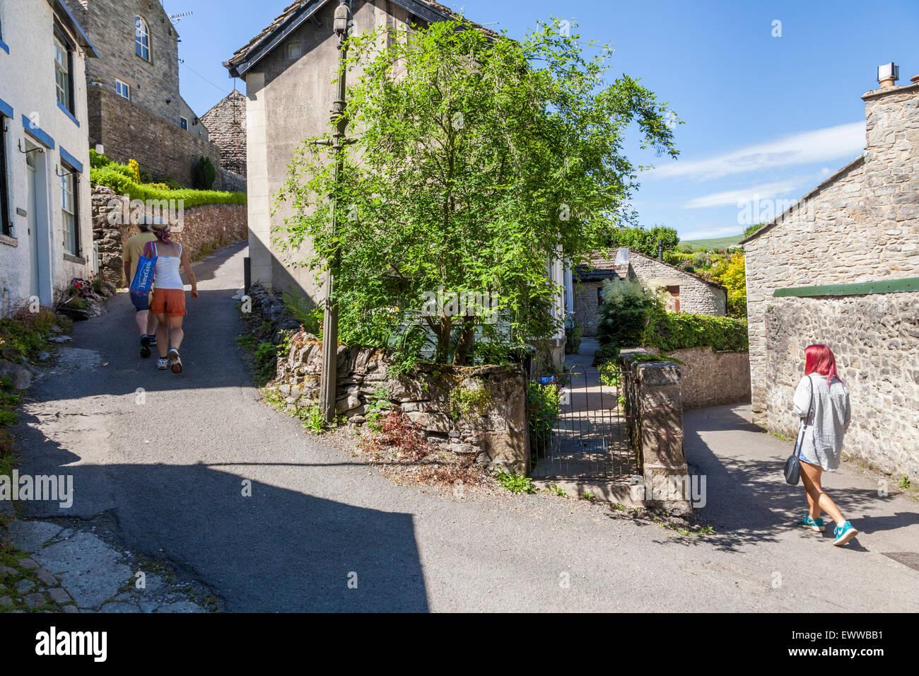 People walking along an English village lane in Summer. Castleton, Derbyshire, Peak District National Park, England, - Stock Image