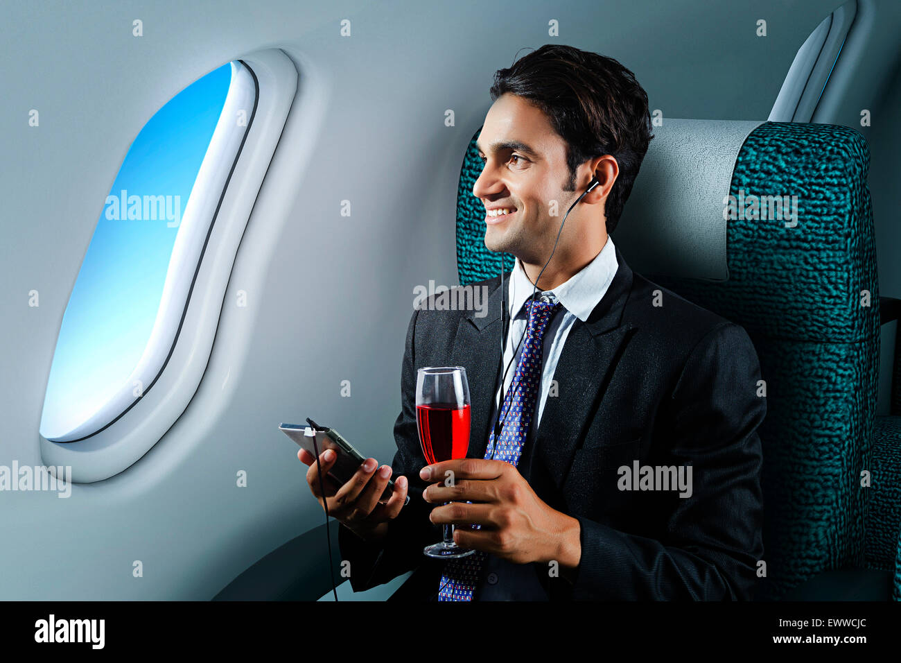 1 indian Business Man Sitting Airplane and Mobile Phone Hearing Music - Stock Image