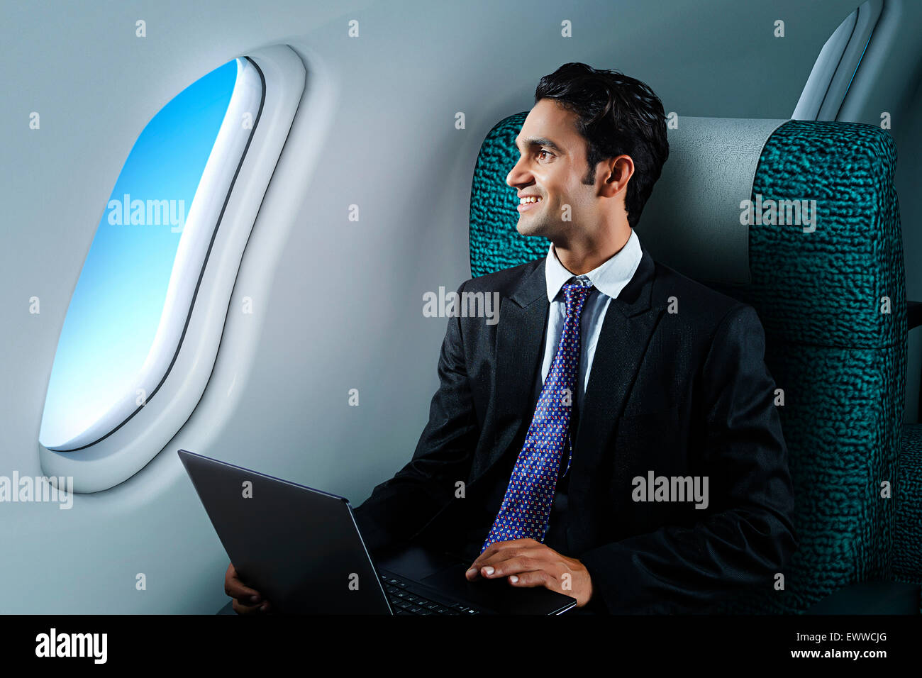 1 indian Business Man Sitting Airplane and laptop working