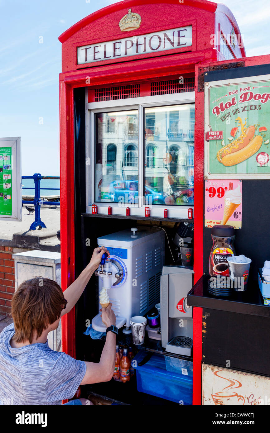 A Man Serves Ice Cream From A Converted Old Red Telephone Box, Eastbourne, Sussex, UK - Stock Image