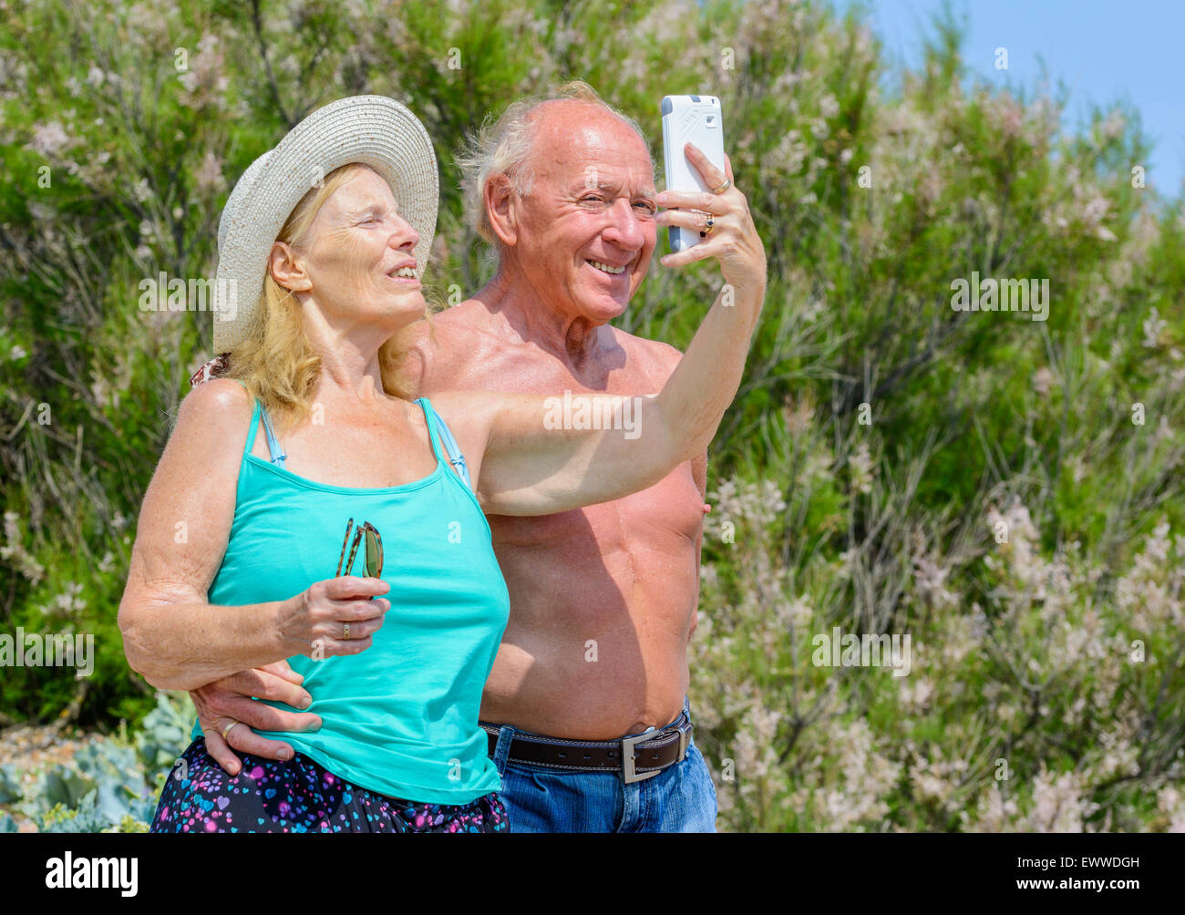 Elderly couple taking a selfie photo of themselves on a hot sunny day in Summer in the UK. Happy elderly couple. - Stock Image