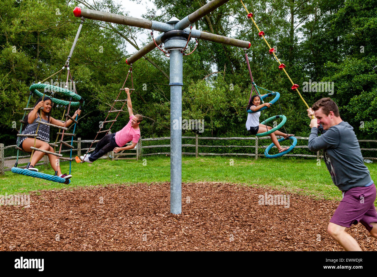 A Family Playing On The Swings, Play Area, Sussex, UK - Stock Image