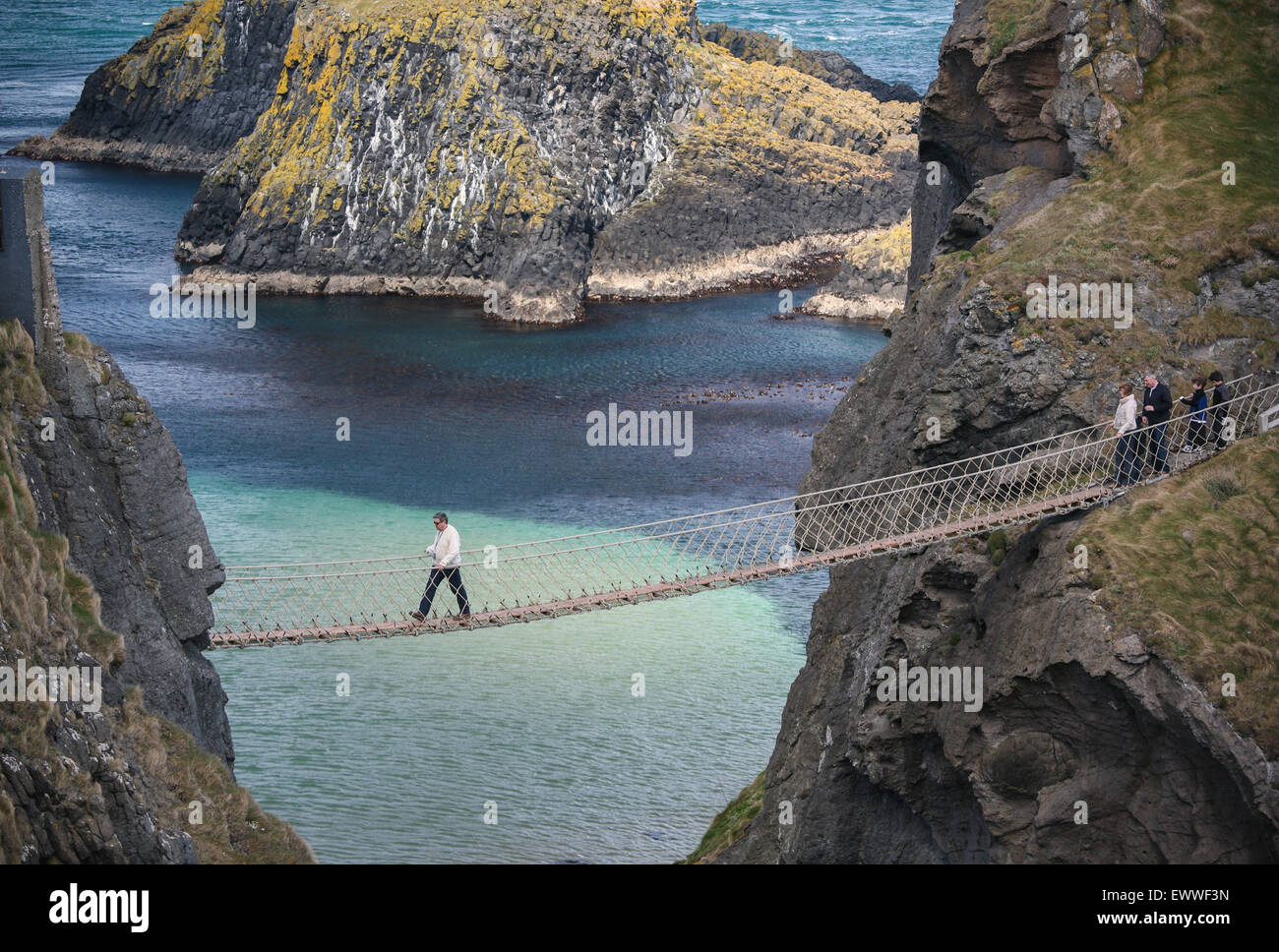 Crossing Carrick a Rede rope bridge, a suspension bridge which spans 20 metres from the mainland to the tiny Carrick - Stock Image