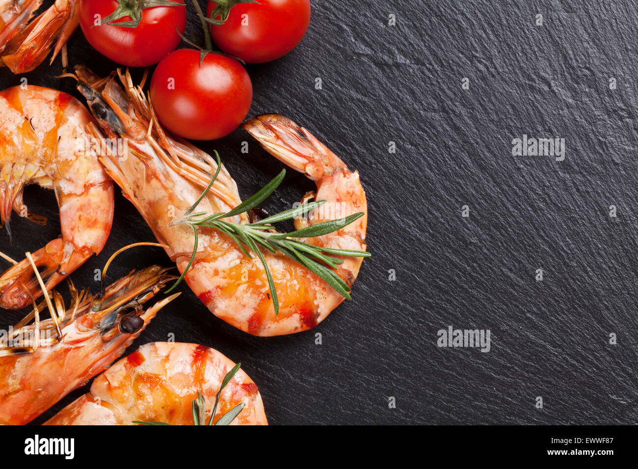 Grilled shrimps on stone plate. Top view with copy space - Stock Image