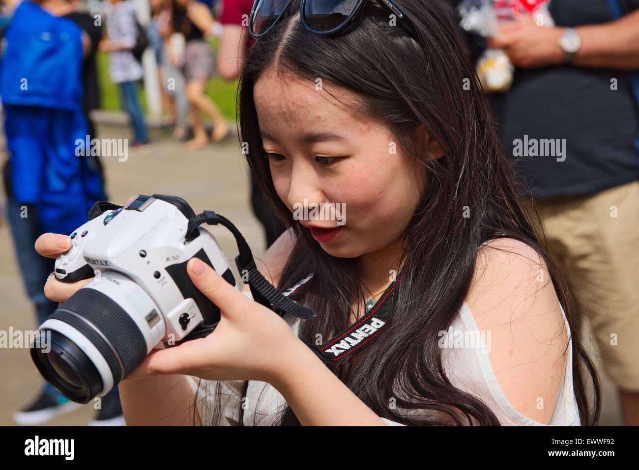 Pretty Asian woman examining screen on SLR digital camera - Stock Image