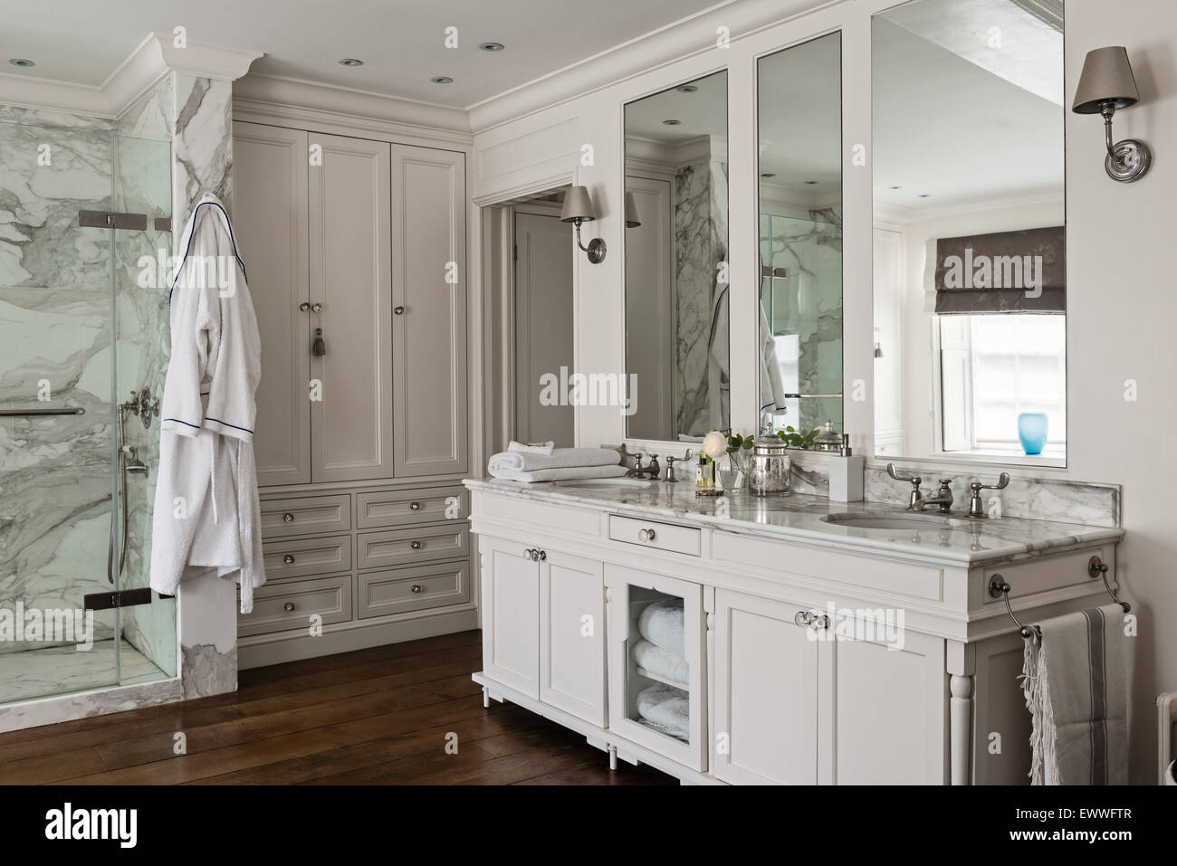 Bathroom with built in storage, polished floorboards and marble surfaces. Stock Photo