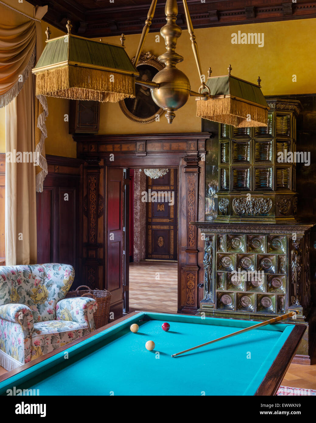 Billiard table in room with tiled stove and chintz upholstered armchair - Stock Image