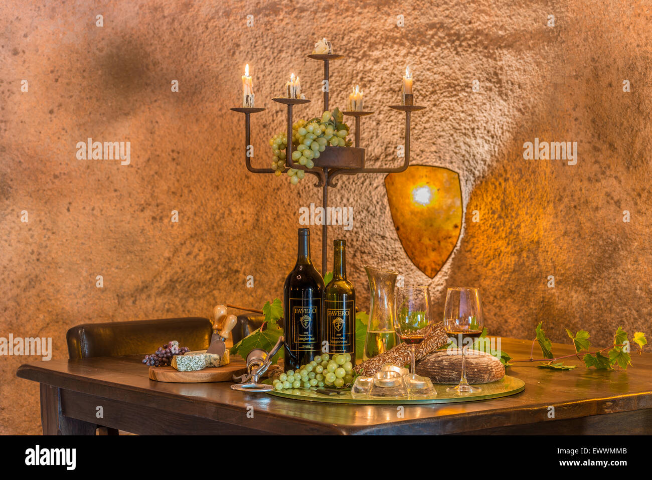 Wine cave featuring a bread, wine, fruit and cheese platter illuminated by rustic candelabra - Stock Image