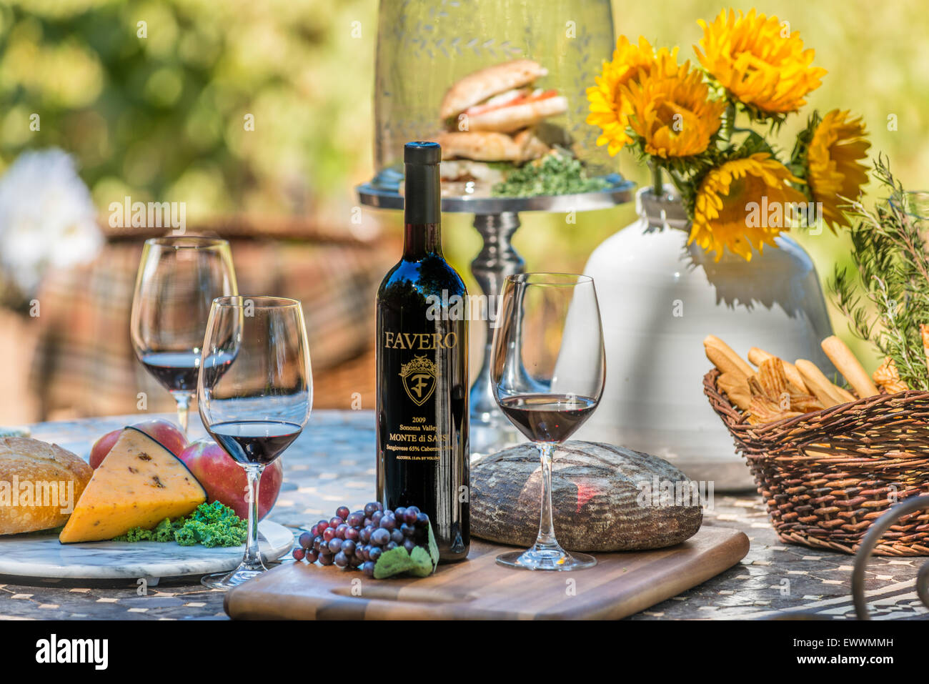Wine & cheese platter on table with sunflowers in Napa Valley - Stock Image