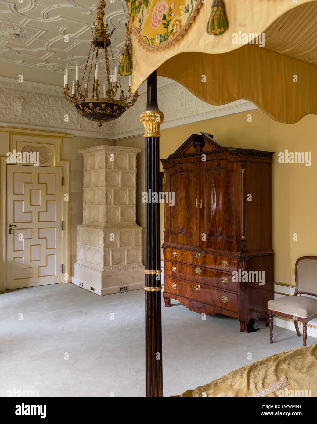 Antique armoire in bedroom with tiled stove, stucco ceiling and four poster bed - Stock Image