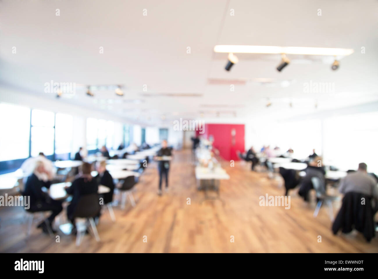 out of focus shot of an office cafeteria, people serving themselves at the counter with table in the foreground, - Stock Image