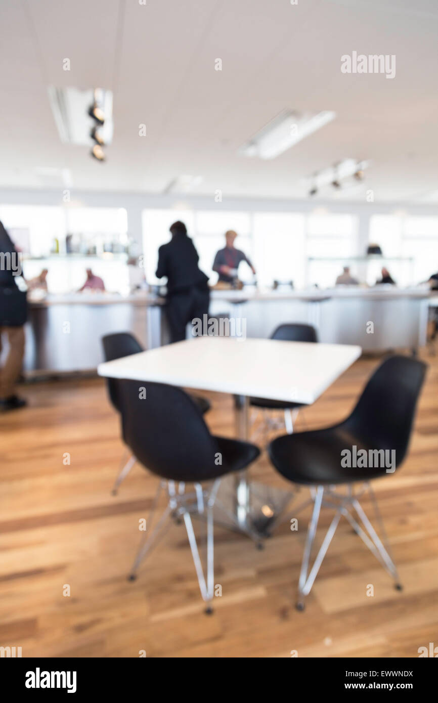 out of focus shot of an office cafeteria, people serving themselves at the counter with table in the foreground - Stock Image