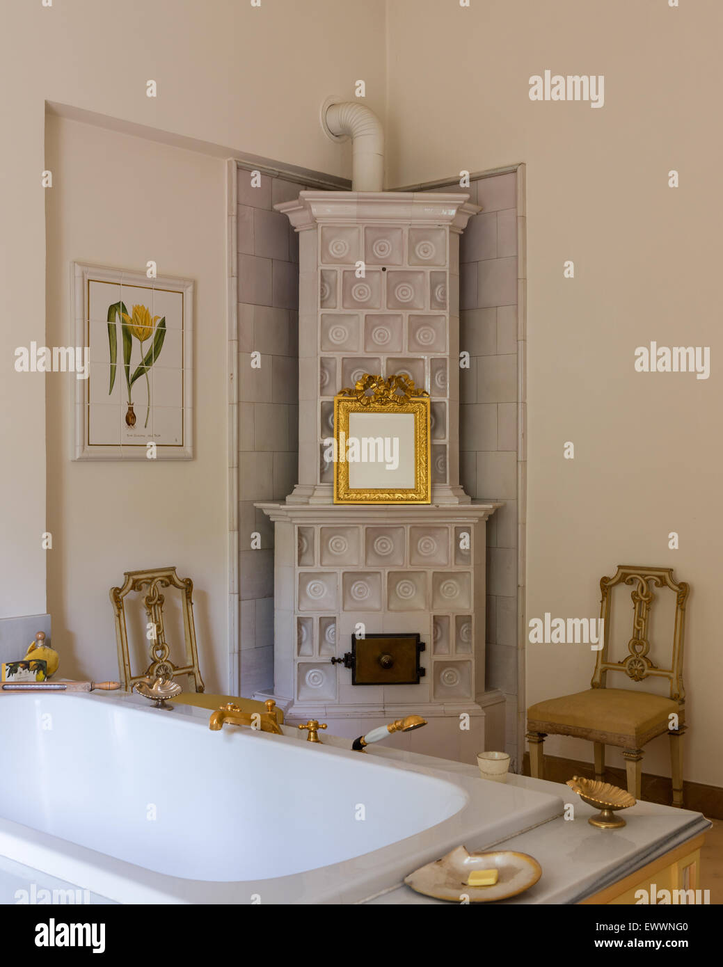 Gilt framed mirror on tiled stove in bathoom with pair of matching antique chairs - Stock Image