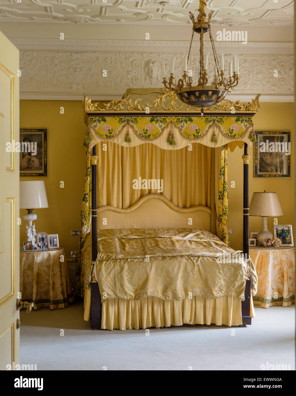 Four poster bed with gilt framework in sumptous bedroom with stucco ceiling - Stock Image