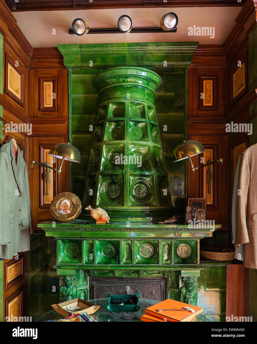 Green tiled stove in study with wood panelled walls and brass wall lights - Stock Image
