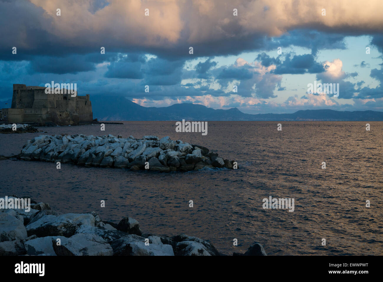 view of the gulf of naples and castel dell'ovo on a cloudy evening - Stock Image