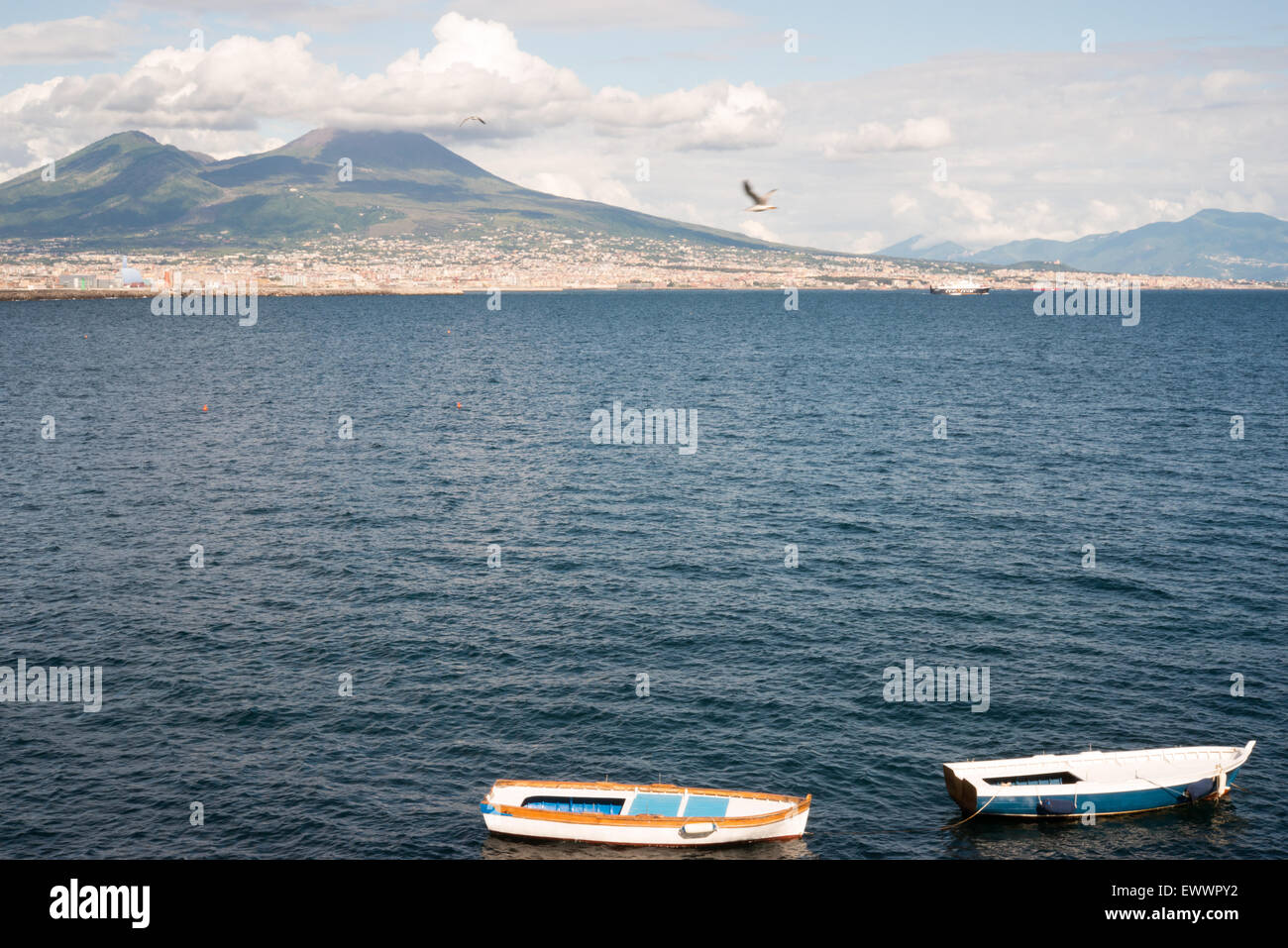 View of the mount Vesuvius, two fishing boats and the Gulf of Naples from Mergellina - Stock Image
