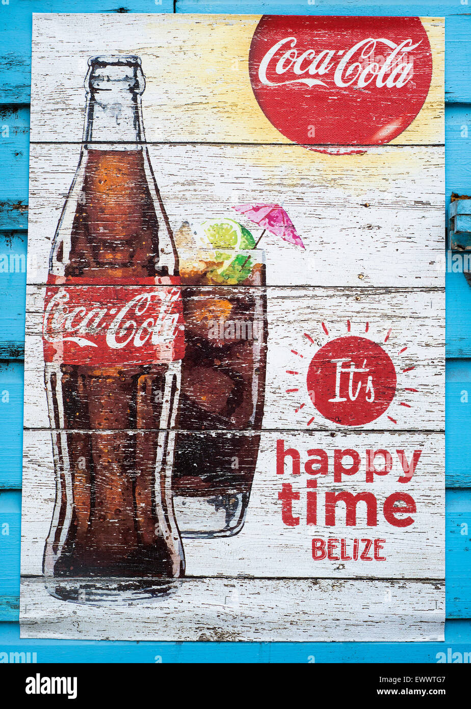 A poster advertisement for coca cola on the side of a wall in Belize. - Stock Image