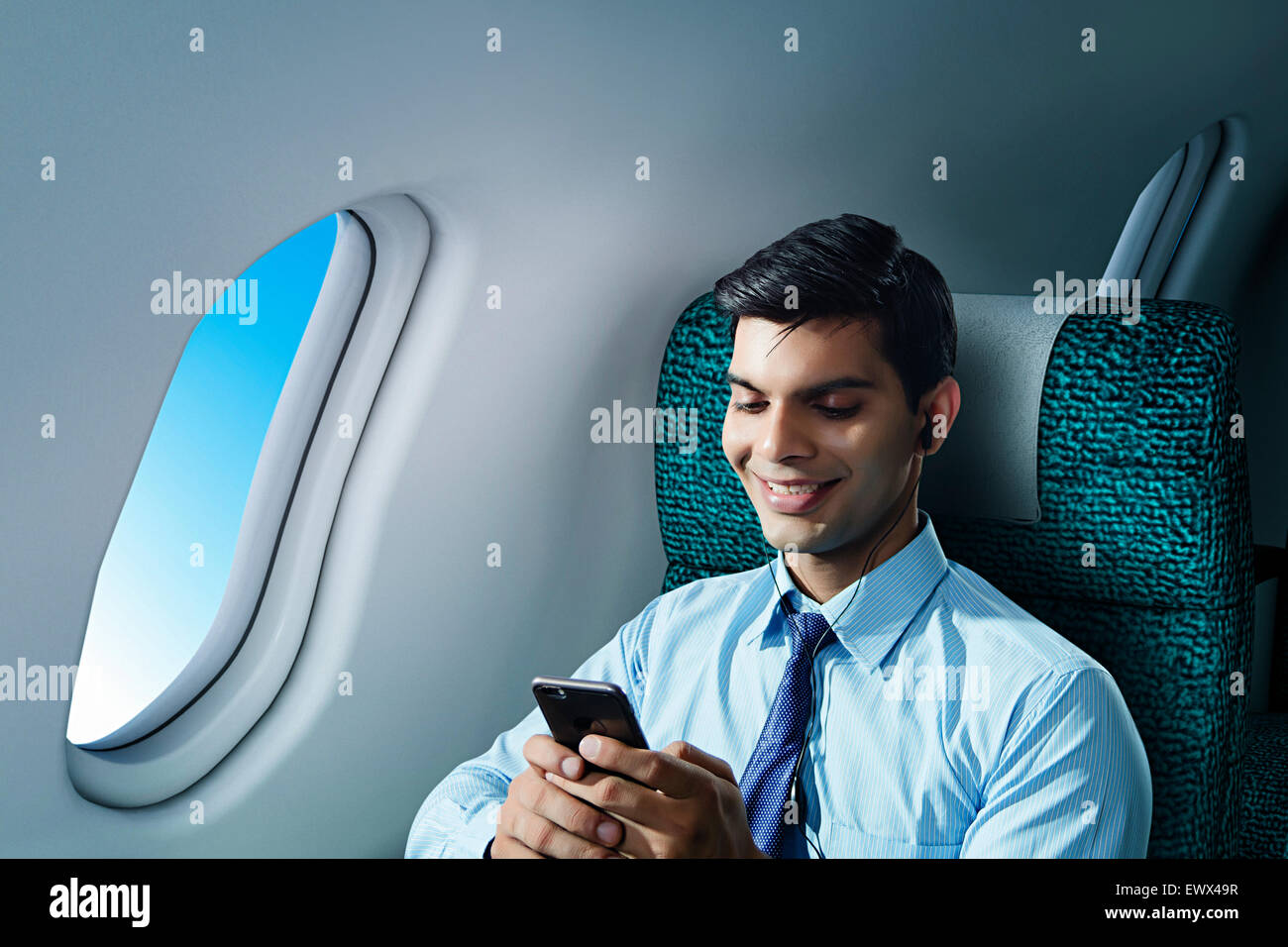 1 Business Man Sitting Aeroplane Cell phone hearing Music - Stock Image