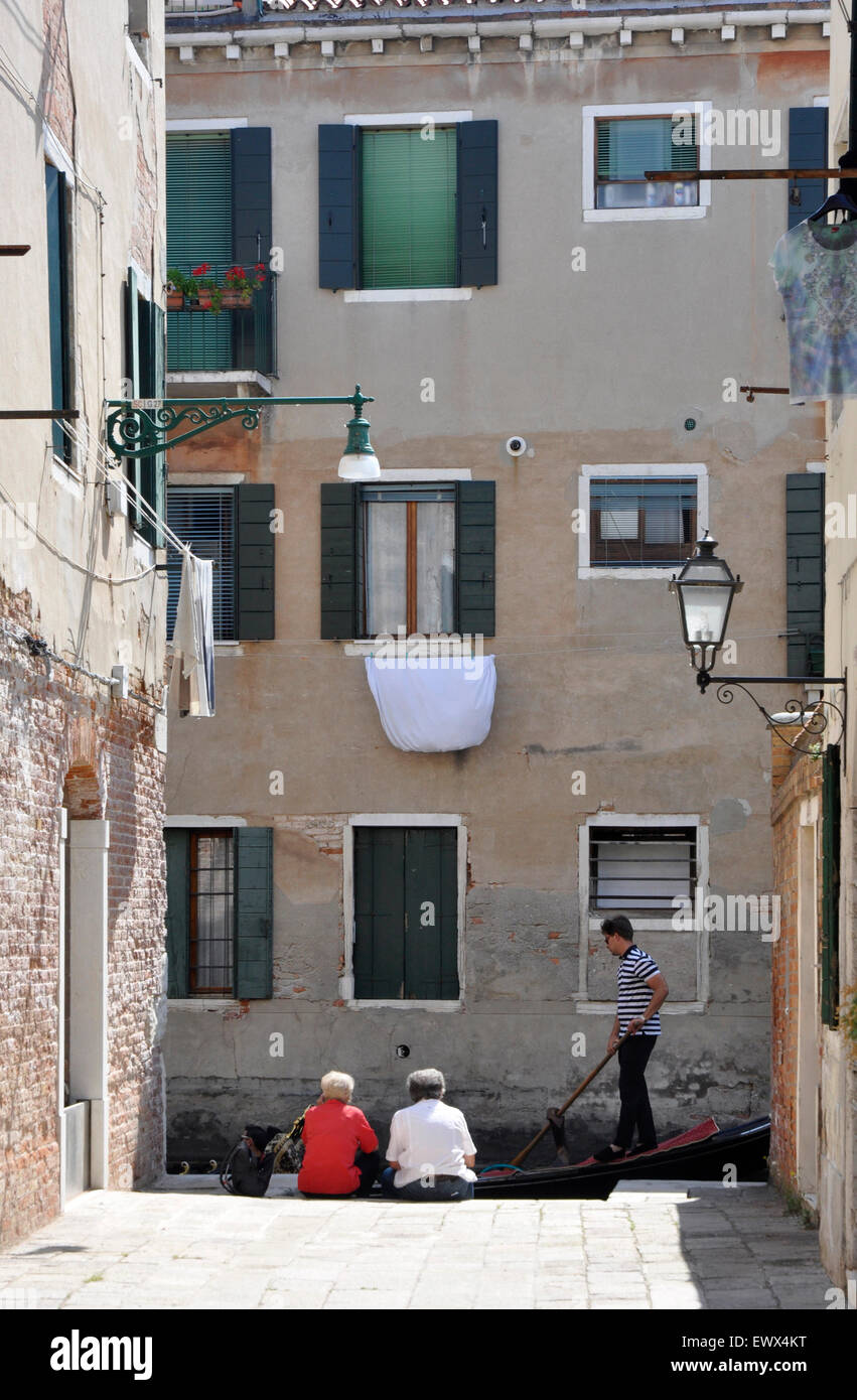Italy Venice - side street - backwater canal Santa Croce area - couple seated - passing gondola - tall houses - - Stock Image