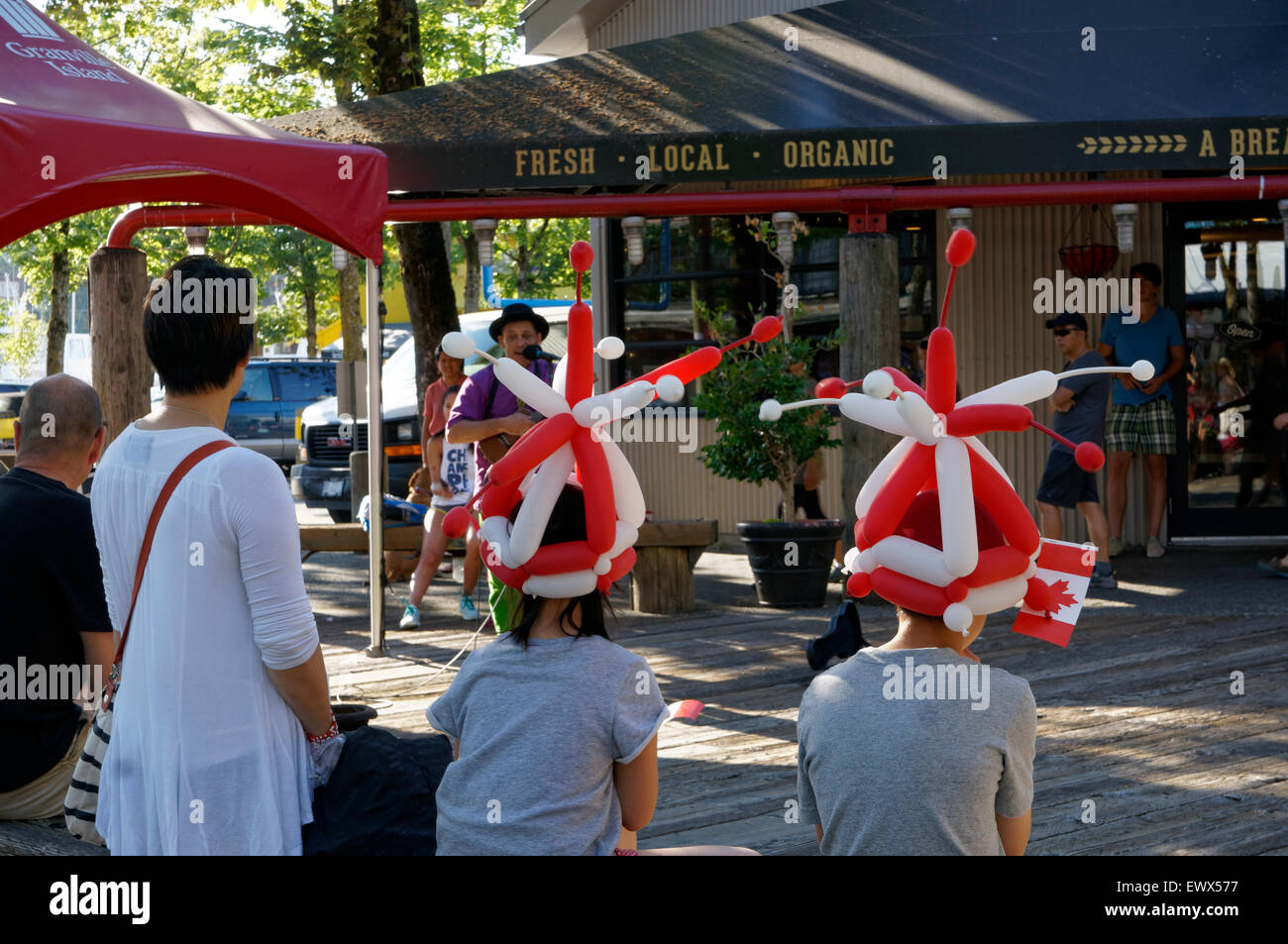 A busker entertains children at Canada Day celebrations on Granville Island in Vancouver, British Columbia, Canada - Stock Image