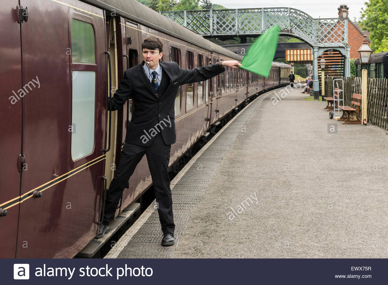 The guard signals that the train is ready to depart from Weybourne Station on the North Norfolk Railway - Stock Image
