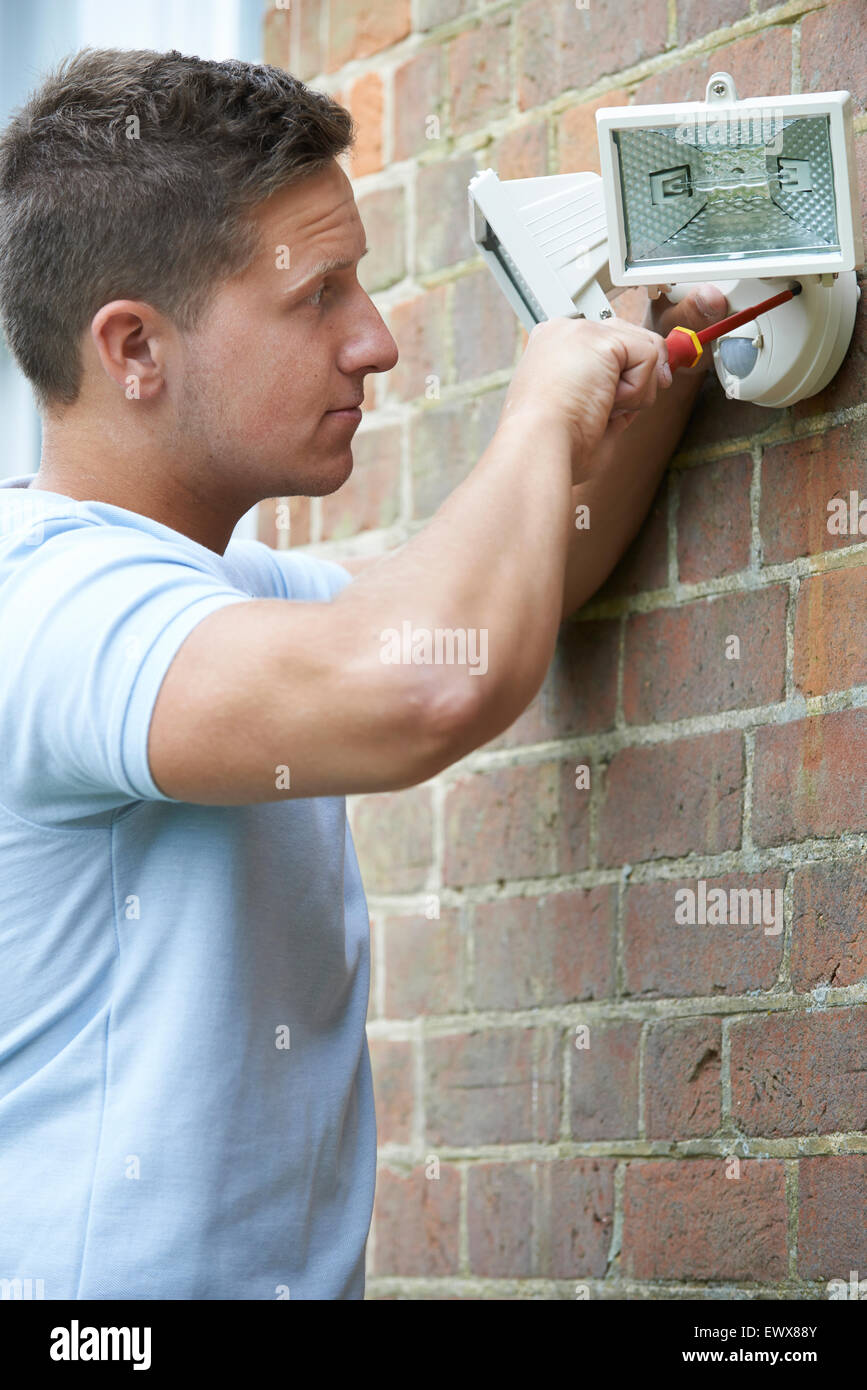 Security Consultant Fitting Security Light To House Wall - Stock Image