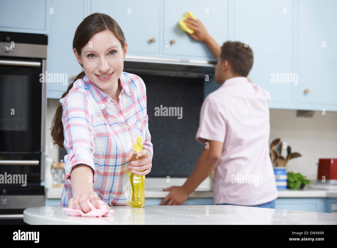 Couple Cleaning Kitchen Surfaces And Cupboards Together Stock Photo